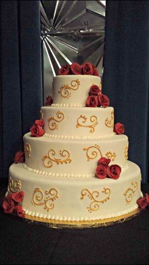 gold scrollwork wedding cake with red rose