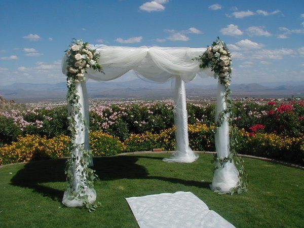 Chuppah with satin draping and tulle overlay has fresh floral accents to create color and dramea