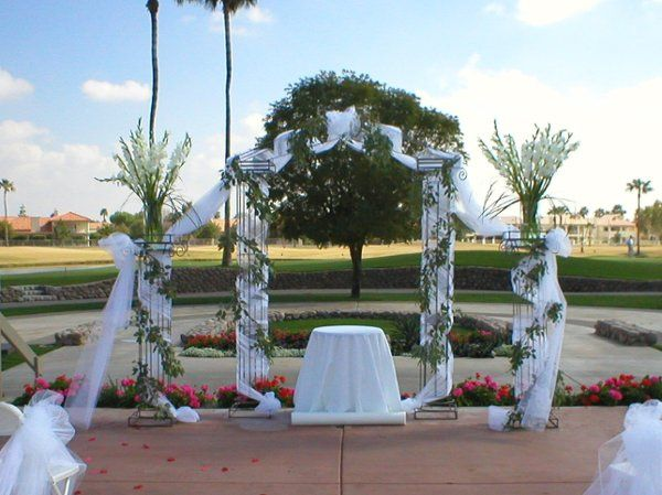 Iron column arch with side columns has added tulle wrap and fresh eucalyptus garland