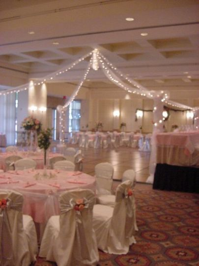 Chair covers with floral additions to the bows softly accent the linens on the guest table and the...