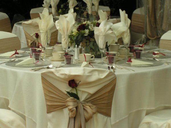 Soft gold bichon chairties and deep burgundy roses accent this beautiful table full of sparkling...