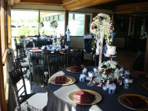 Multiple design centerpieces are enhanced by the sheen of black lamour linens and gold chargers