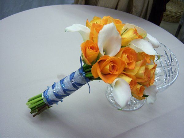 ivory calla lilies and bright orange roses are the perfect foil for the periwinkle french handle...