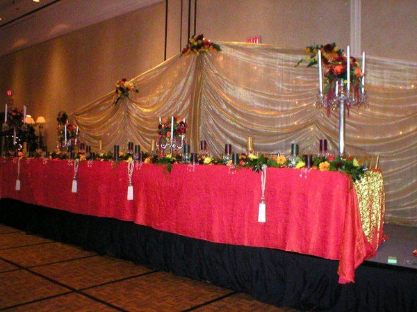 Crushed orange sunset linens,  beautiful floral accentsm crystals and tassels create and elegant...