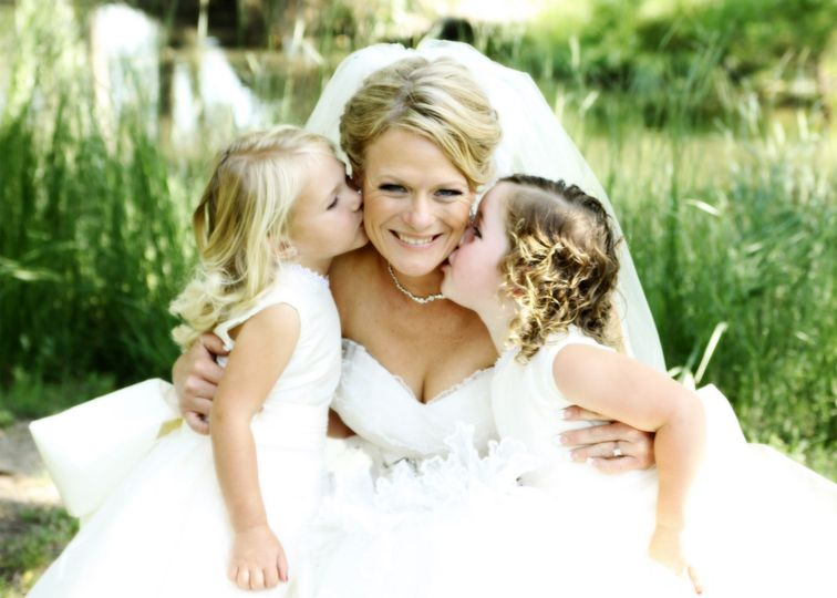 Bride with flower girl kiss