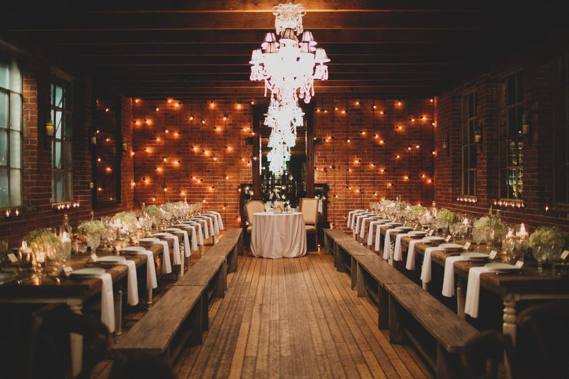Beautiful and romantic reception space at Carondelet House with farmhouse table settings spaced with...