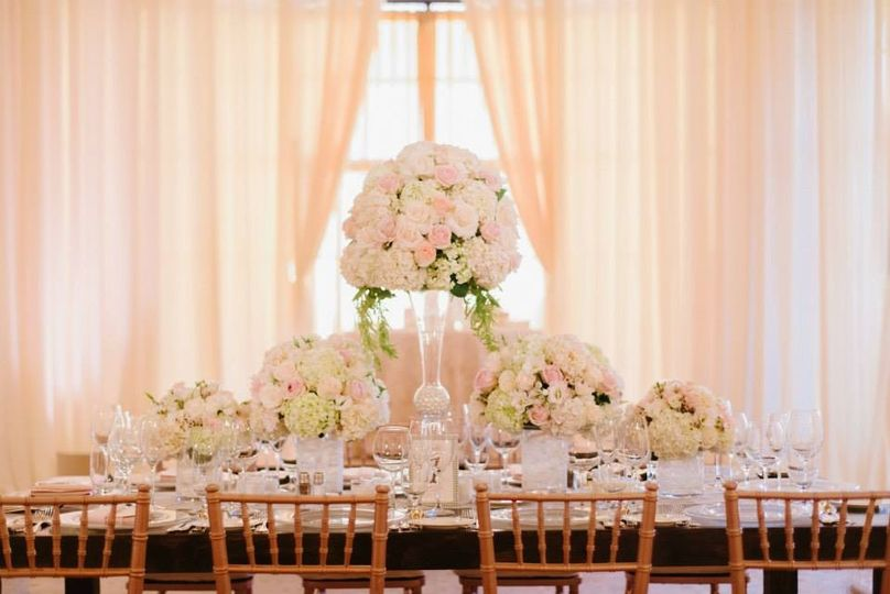 Lush and bright tablescape with centerpieces of differing heights. Designed with blush and white...