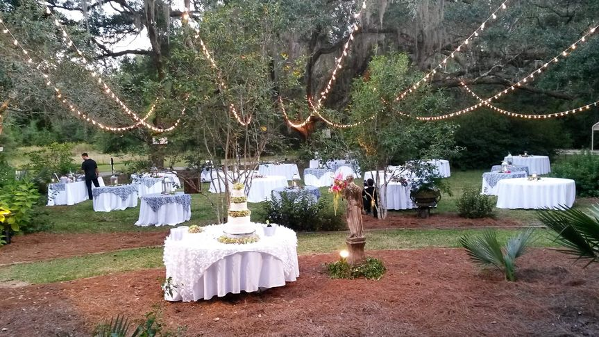 Front lawn with lights strung from upstairs porch to the live oak trees, spotlighting the wedding...