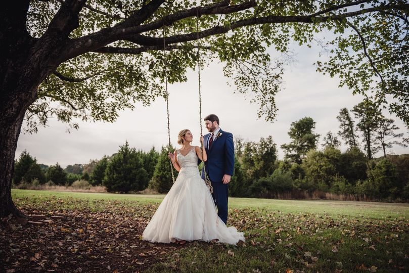 bride sitting on a swing with her groom