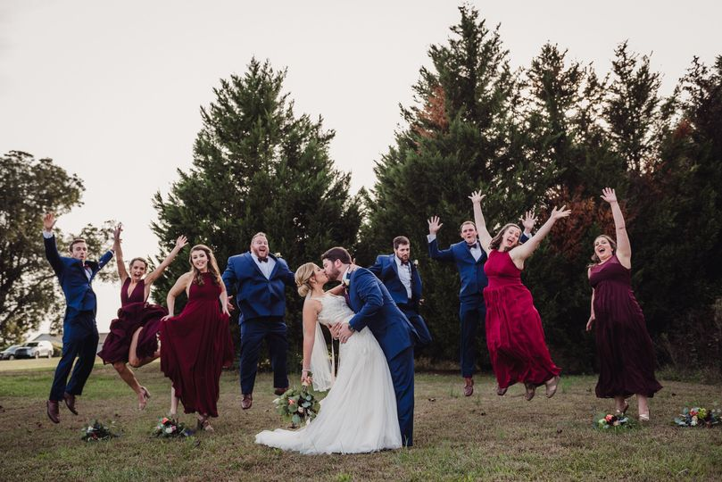 the bridal party jumping in the air behind the bri