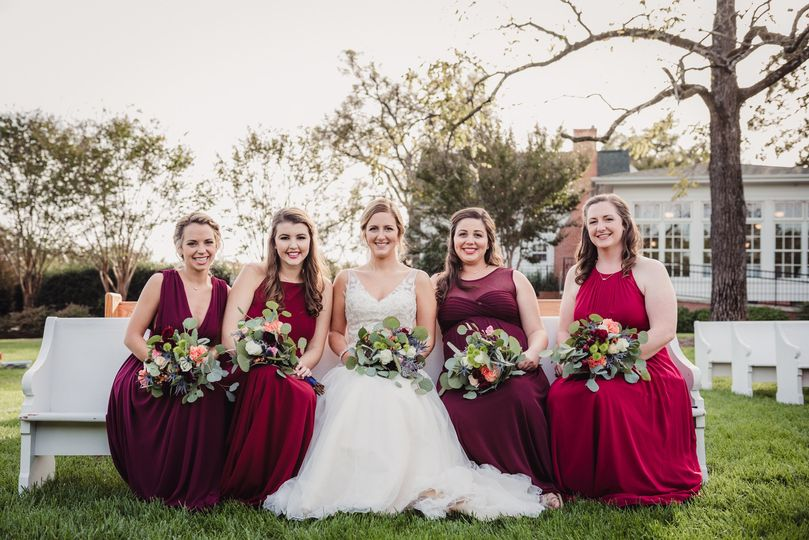the bridesmaids and bride sitting outside on a chu