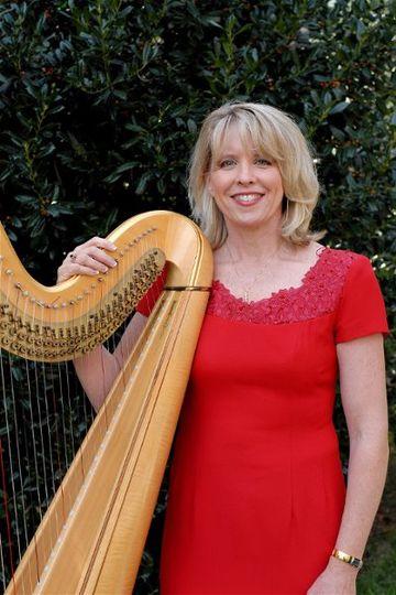 Kansas City Harpist, Dedra Coffee, standing by her harp after an outdoor wedding ceremony....