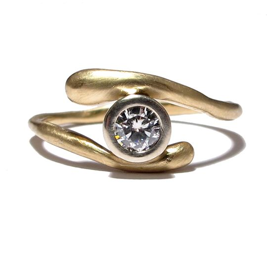 This yellow gold organically shaped band features a 3mm bezel set Moissanite. You can order this...