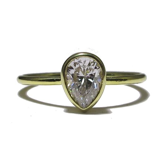 This yellow gold ring features a bezel set pear diamond, approximately .75 carats. Simple and...