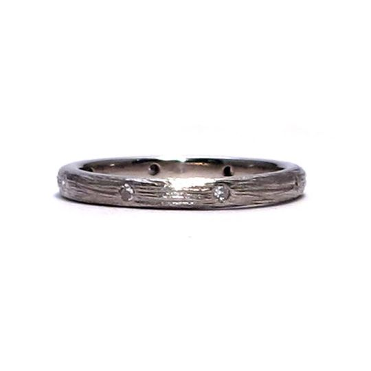 This textured white gold band features eight tiny diamonds evenly spaced around the ring. It is also...