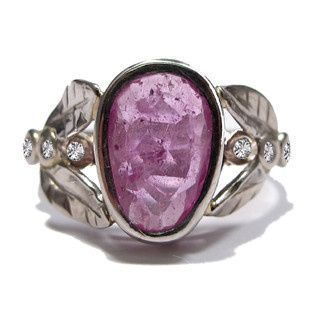 This organic leafy ring features a natural pink sapphire, weighing over 1 carat, with three diamonds...
