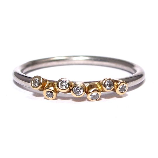 This edgy yet gorgeous ring features 7 diamonds bezel set in yellow gold with a round wire palladium...