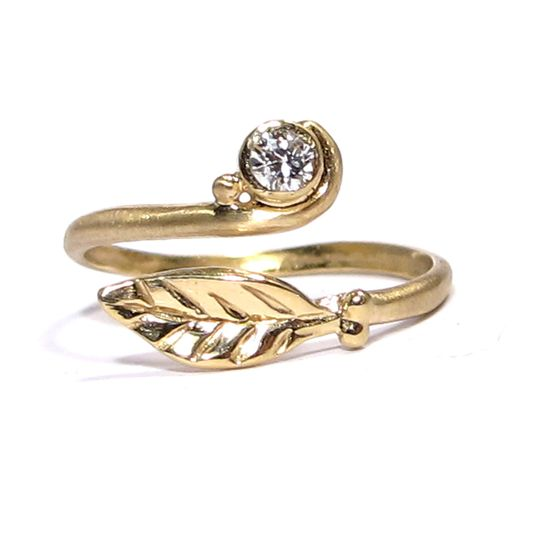 This leafy organic ring features a 3mm diamond bezel set in yellow gold.