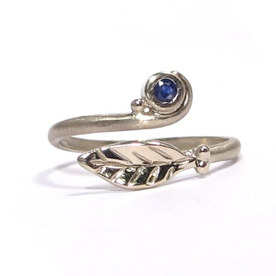 This organic leaf ring is made of 18K white gold and features a 1.mm, .015 carat blue sapphire.