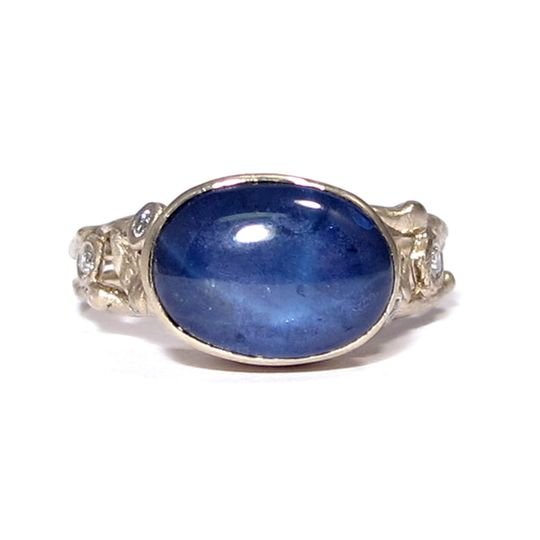 This organic leafy engagement ring features an oval star sapphire with two white diamonds on each...