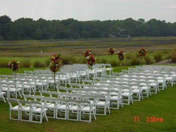 Outside ceremony overlooking the golf course at Colleton River.  Flowers were designed in decorative...