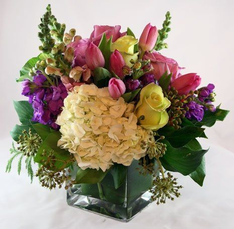 Floral arrangement designed in glass vases lined with decorative green leaf.  Hydrangeas, roses,...