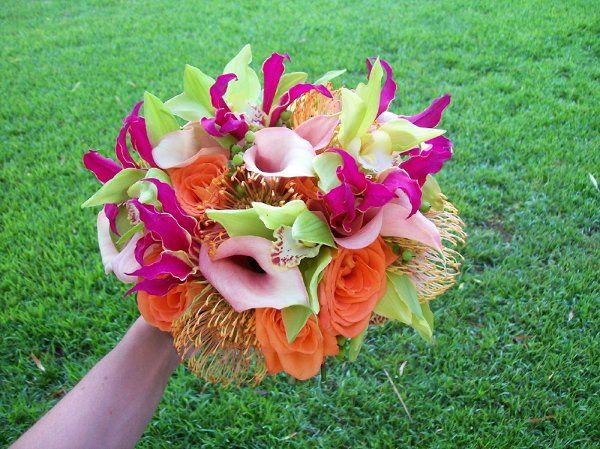 Stem style bouquet designed with pink mini callas, orange roses, green cymbidium orchid blooms.