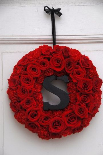 A wreath of red roses and carnations surround the couple's initial.