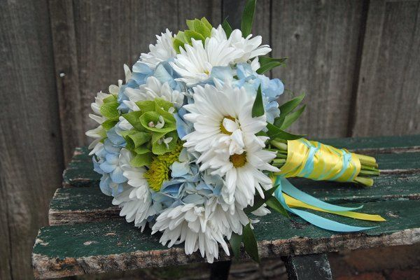 Bride's bouquet of blue hydrangea, white daisy pomps, green button mums, bells of Ireland, and...