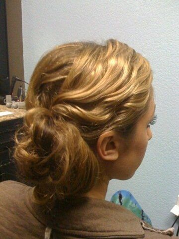 Bride is lacing fresh flowers on side of bun for wedding day in January. They will be thredded in...