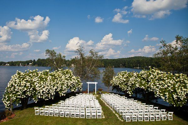 An outdoor ceremony site with white garden chairs.