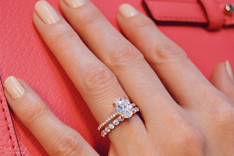 Custom oval cut diamond engagement ring and custom eternity diamond wedding band in rose gold