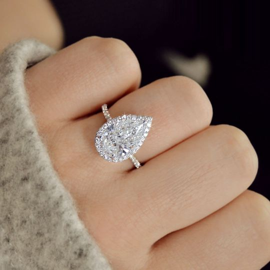 Pear shaped halo diamond engagement ring with a thin band in 18k white gold
