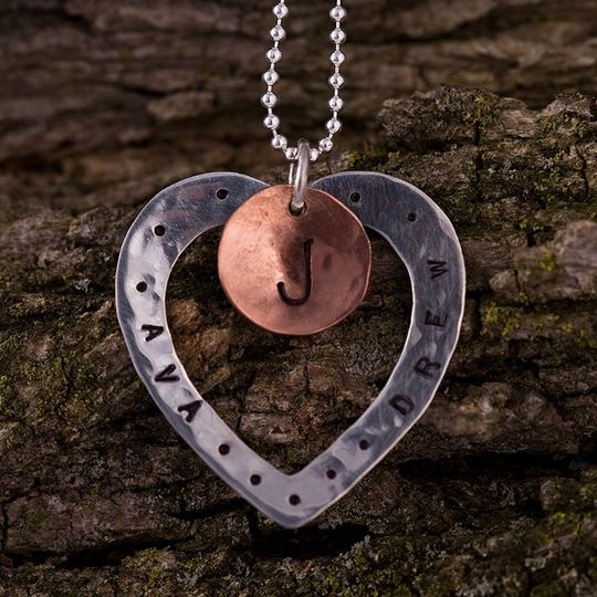 A sterling silver heart washer is paired with a small copper disc. Both pieces have been...