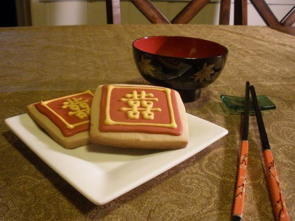 """Cookies for a Chinese wedding, showing the """"Double Happiness"""" symbol in gold over a traditional red..."""