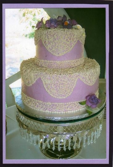 Small 2 tier Buttercream cake with Light and dark Lilac colored Gumpaste flowers.