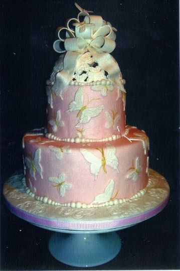 Pale Pink Fondant covered 2 tiered Wedding Cake.  Fondant Bow with Gumpaste Butterflies.