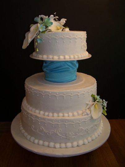 Buttercream Wedding Cake with White and pale Teal flowers.  Teal cuff separates the tiers.