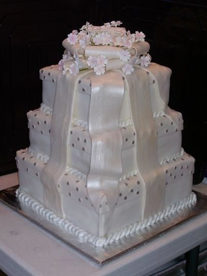 White Pearl Fondant Stacked Boxes.  Fondant Bow with Gumpaste flowers on top.