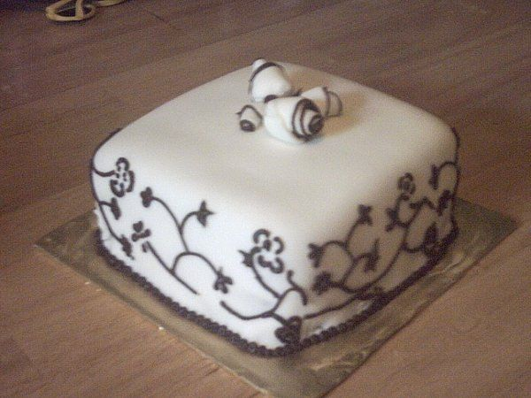 Fondant covered cake with fondant roses and chocolate scrollwork on the sides. This would be a nice...
