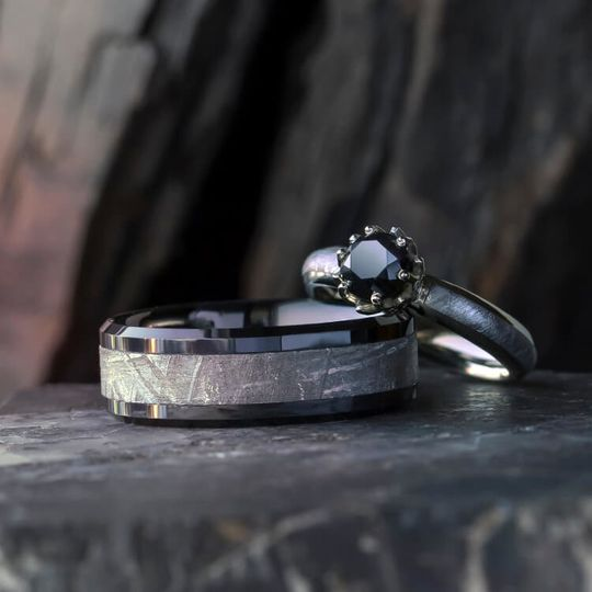 A black diamond shimmers in its white gold lotus setting, which shares a matching meteorite inlay...
