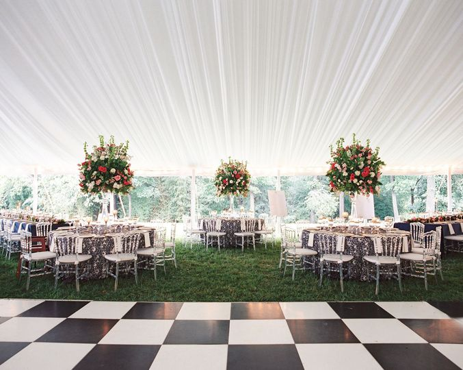 Black and white dance floor pops with the handpleated white fabric lining this wedding tent.