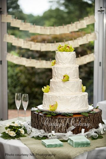 Rustic buttercream wedding cake with fresh orchids on tree slice cake stand.