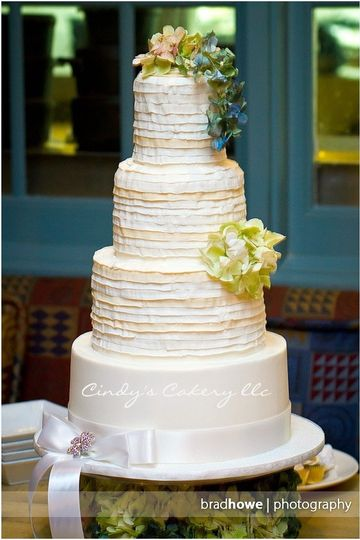 Pleated buttercream wedding cake with satin ribbon and brooch.  Fresh floral topper.
