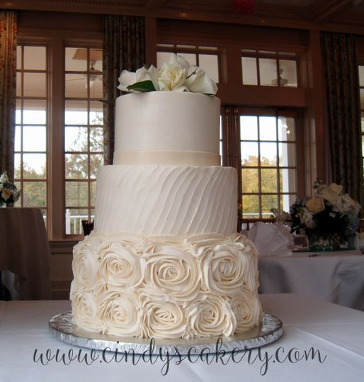 Buttercream wedding cake with rosettes, diagonal flutes and fondant ribbon. Fresh floral topper