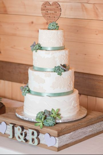 Buttercream wedding cake with fondant lace appliques and fresh succulents