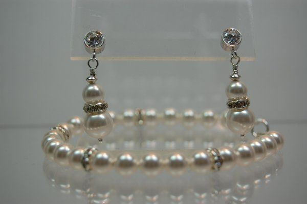 This elegant bracelet of 8mm Swarovski Crystal Pearls and Rhinestone spacers is set with a sterling...
