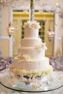 Four tier wedding cake topped with flowers