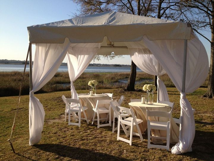 A cabana with tables for guests to enjoy the view of the water.