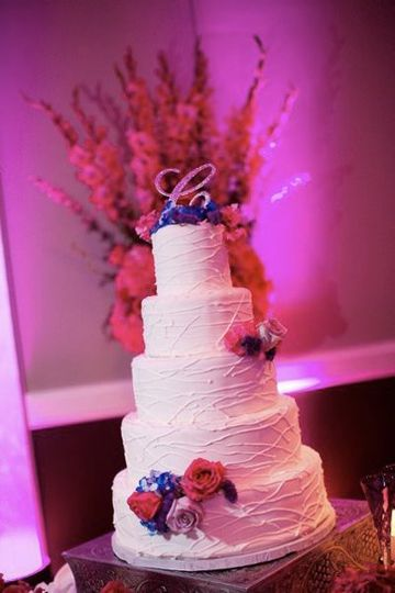 White wedding cake with pink and blue decoration